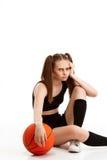 Muchacha bonita joven que presenta con baloncesto sobre el fondo blanco Foto de archivo
