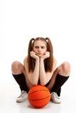 Muchacha bonita joven que presenta con baloncesto sobre el fondo blanco Imagen de archivo