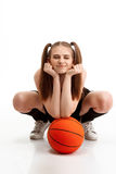 Muchacha bonita joven que presenta con baloncesto sobre el fondo blanco Fotografía de archivo libre de regalías