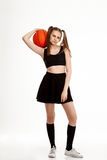 Muchacha bonita joven que presenta con baloncesto sobre el fondo blanco Imagenes de archivo