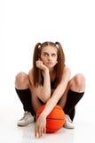 Muchacha bonita joven que presenta con baloncesto sobre el fondo blanco Foto de archivo libre de regalías