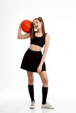 Muchacha bonita joven que presenta con baloncesto sobre el fondo blanco Fotografía de archivo