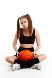 Muchacha bonita joven que presenta con baloncesto sobre el fondo blanco Imagen de archivo libre de regalías