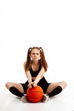 Muchacha bonita joven que presenta con baloncesto sobre el fondo blanco Imágenes de archivo libres de regalías