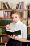 Muchacha bonita joven que presenta en la cámara en la biblioteca Concepto de la educación Foto de archivo libre de regalías