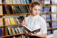 Muchacha bonita joven que presenta en la cámara en la biblioteca Concepto de la educación Fotografía de archivo libre de regalías