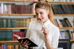 Muchacha bonita joven que presenta en la cámara en la biblioteca Concepto de la educación Imagen de archivo libre de regalías