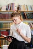 Muchacha bonita joven que presenta en la cámara en la biblioteca Concepto de la educación Foto de archivo