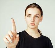Muchacha bonita joven que señala en el fondo blanco, concepto de la gente de la ciencia del negocio Foto de archivo