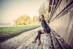 Muchacha bonita joven que se sienta en banco en parque fotografía de archivo libre de regalías