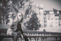 Muchacha bonita joven que se sienta en banco en parque imagen de archivo libre de regalías