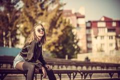 Muchacha bonita joven que se sienta en banco en parque foto de archivo