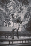 Muchacha bonita joven que se sienta en banco en parque fotografía de archivo