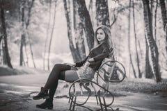 Muchacha bonita joven que se sienta en banco en parque fotos de archivo