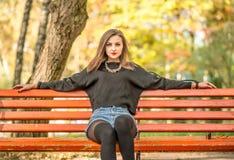 Muchacha bonita joven que se sienta en banco en parque imagenes de archivo