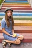 Muchacha bonita joven que se sienta en los pasos de piedra multicolores Fotografía de archivo