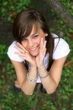 Muchacha bonita joven que sonríe en la hierba. Foto de archivo libre de regalías