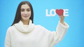 Muchacha bonita joven vestida en la ropa blanca Durante este tiempo se coloca en un fondo azul Lleva a cabo una palabra del amor  almacen de metraje de vídeo