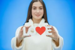 Muchacha bonita joven vestida en la ropa blanca Durante este tiempo se coloca en un fondo azul Lleva a cabo una palabra del amor  imagen de archivo libre de regalías