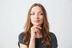Muchacha bonita juguetona joven que mira en lado con la mano en la barbilla sobre el fondo blanco Fotos de archivo libres de regalías