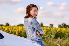 Muchacha bonita pensativa que la inclina detrás contra el coche Fotos de archivo libres de regalías