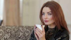 Muchacha bonita pensativa que se sienta en el café con la taza de té almacen de metraje de vídeo