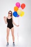 Muchacha bonita positiva que sostiene los globos coloridos y los pequeños macarrones Fotografía de archivo libre de regalías