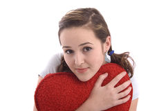 Muchacha bonita que abraza un corazón rojo grande de la felpa Fotografía de archivo