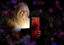 Muchacha bonita que abre el rectángulo de regalo rojo de la Navidad Foto de archivo