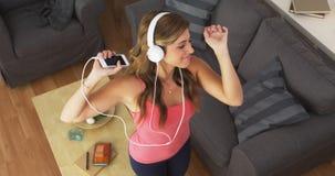 Muchacha bonita que baila a la música con smartphone Fotografía de archivo libre de regalías