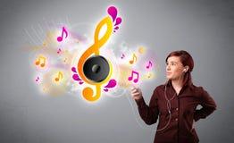Muchacha bonita que canta y que escucha la música con las notas musicales Foto de archivo