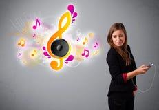Muchacha bonita que canta y que escucha la música con las notas musicales Imagen de archivo libre de regalías
