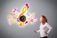 Muchacha bonita que canta y que escucha la música con las notas musicales Fotografía de archivo
