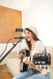 Muchacha bonita que canta y que toca la guitarra Imagen de archivo libre de regalías