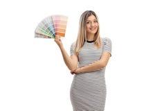 Muchacha bonita que celebra una muestra y una sonrisa del color Fotos de archivo