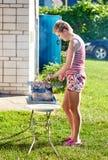 Muchacha bonita que cocina la barbacoa al aire libre Imagen de archivo