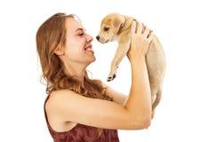 Muchacha bonita que coge el pequeño perrito Imagen de archivo libre de regalías