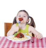 Muchacha bonita que come las pastas y las albóndigas Imagenes de archivo