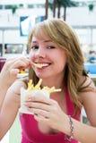 Muchacha bonita que come las patatas fritas Fotos de archivo libres de regalías