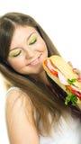 Muchacha bonita que come un emparedado Foto de archivo libre de regalías