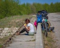 Muchacha bonita que completa un ciclo en la naturaleza salvaje en el camino de tierra Bikes a la muchacha de ciclo La muchacha mo Fotos de archivo