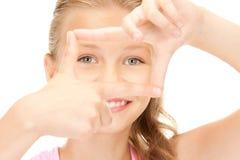 Muchacha bonita que crea un marco con los fingeres Foto de archivo libre de regalías