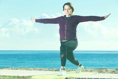 Muchacha bonita que ejercita en la estera del ejercicio Fotos de archivo libres de regalías