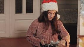 Muchacha bonita que envuelve la caja de regalo Chica joven en el jersey que se prepara para la Navidad almacen de video