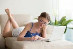 Muchacha bonita que estudia en casa con el ordenador portátil, escribiendo notas, uno mismo-ed Imagen de archivo