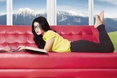 Muchacha bonita que estudia en el sofá Fotos de archivo libres de regalías