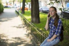 Muchacha bonita que habla ansiosamente en el teléfono celular mientras que se sienta al aire libre Fotografía de archivo