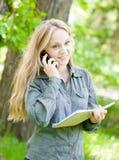 Muchacha bonita que habla en el teléfono con el cuaderno Fotografía de archivo