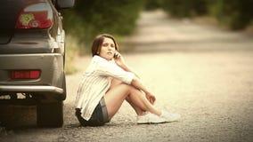 Muchacha bonita que habla por el teléfono después de incidente del coche metrajes