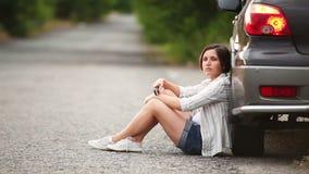 Muchacha bonita que habla por el teléfono después de incidente del coche